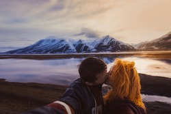 couple red-haired girl and man kissing on the background nature winter snow-capped mountains of Svalbard, Longyearbyen, Spitsbergen, Norway at the time of fire rolled reflection ocean wallpaper love