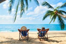 Couple relax on the beach enjoy beautiful sea on the tropical island. Summer beach vacation concept