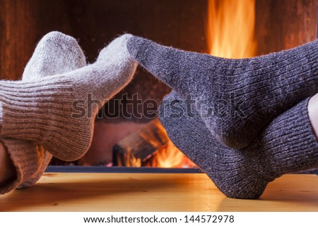 couple relaxing at the fireplace on winter evening