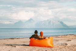 Couple relaxing in air lounger on beach enjoying sea and mountains view traveling together man and woman family lifestyle summer vacations outdoor in Norway