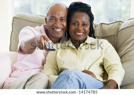 Couple relaxing in living room holding remote control and smiling - stock photo