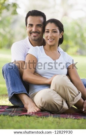 Couple relaxing in park sitting on blanket