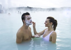 Couple relaxing in the thermal pool of Blue Lagoon. Iceland. Woman puts a mask of white mineral clay on man face.