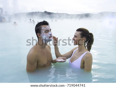 Couple relaxing in the thermal pool of Blue Lagoon. Iceland. Woman puts a mask of white mineral clay on man face. #719044741