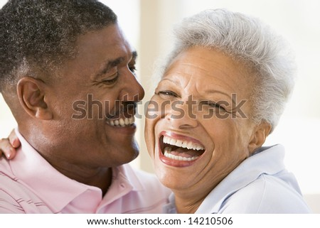 Couple relaxing indoors laughing