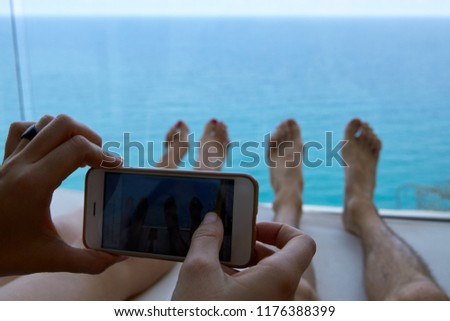 couple relaxing on a deck chair making a photo