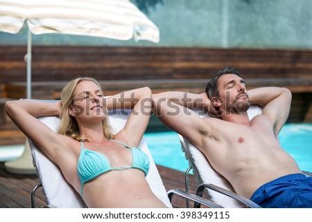 Shutterstock Couple relaxing on a sun lounger near pool