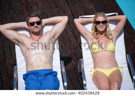 Couple relaxing on a sun lounger near the pool #402438628