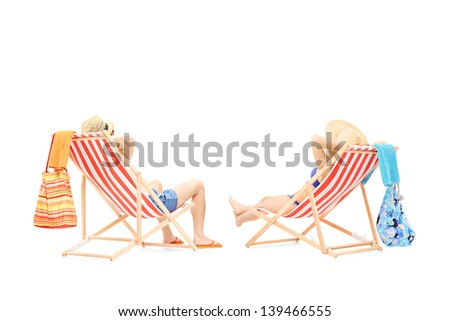 Couple relaxing on a sun loungers, isolated on white background