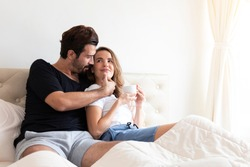 Couple relaxing on bed at home. Lover cuddling and embracing while sitting in bed in the morning. Romantic couple sitting on bed in bedroom. Young married Couple relaxing in bed with hot drink.