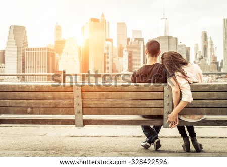 couple relaxing on New york bench in front of the skyline at sunset time. concept about love,relationship, and travel  #328422596
