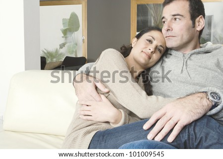 Couple relaxing on sofa at home, holding each other.