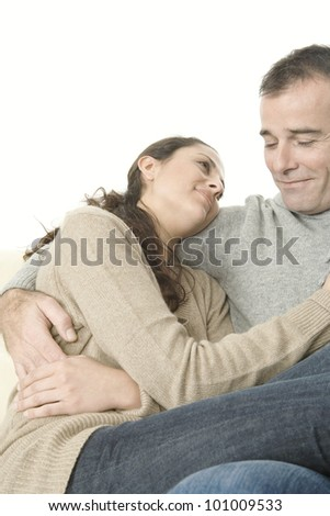 Couple relaxing on sofa at home holding each other, smiling.