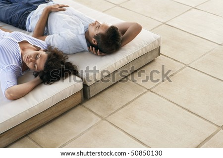 Couple relaxing on sun beds on terrace, elevated view