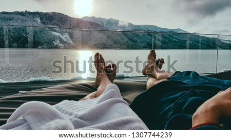 Couple relaxing on the sun beds in Spa, Badehaus Millstätter See, Austria, by Millstätter See. Only the legs are visible and some parts of bathrobes. Snowy mountains in the back, snow on the terrace