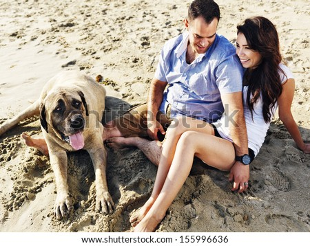 couple relaxing with pet dog on the beach.