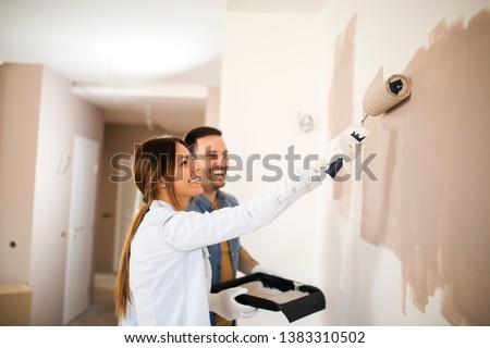 Couple renovating their apartment while man holding painting container and woman painting walls with roller in light brown color. #1383310502