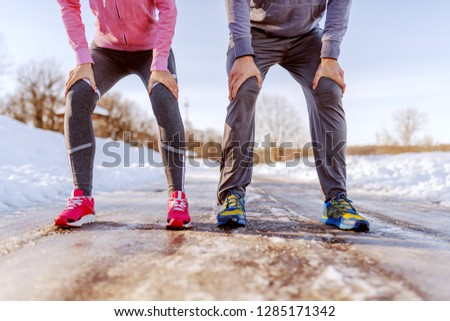 Couple resting from running. Cropped picture. Winter fitness concept.