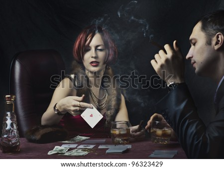 Couple - rich woman and man in suit playing poker, drink whiskey and smoke cigar. Retro style