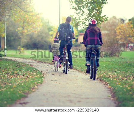 couple ride bicycles in the meadow back to camera