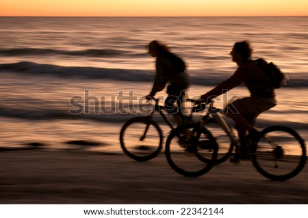 Couple riding bycicle at sunset in Honeymoon Island, Florida.