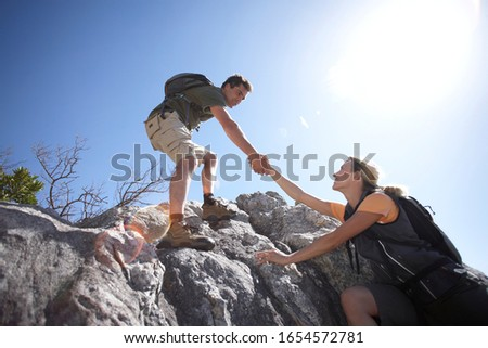 Couple rock climbing together on a sunny day