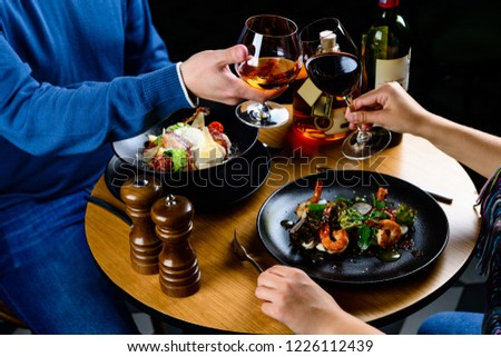 couple romantic dinner, close up of hand with glasses in a restaurant