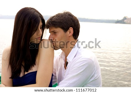 Couple romantic love moment during sunset on a lake