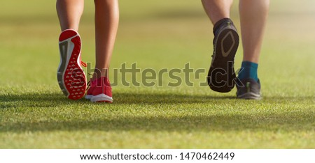 Couple runners athletes feet running on grass. Female  male fitness sunlight jogging workout. Sport athlete active lifestyle concept. Athletic pair of legs running on grass during sunset city park