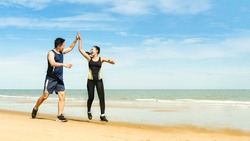 couple runners jump and touch hands And congratulate when able to practice according to the exercise program,Athletes practice running at the seaside And happy when successful in the training program
