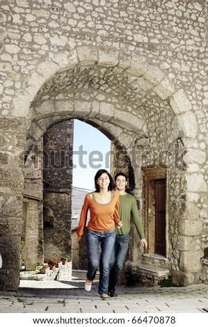 Couple runnin through the gate of an italian village