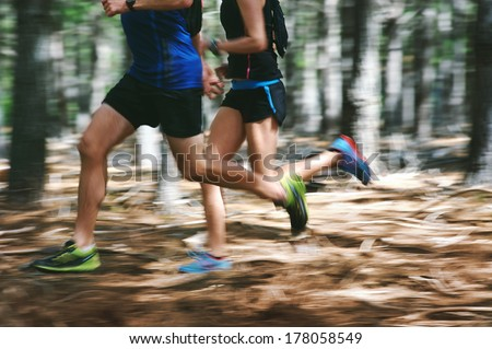 Couple running fast through the forest on trail run with motion blur #178058549