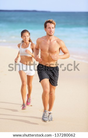 Couple running - man fitness runner first. Runners in jogging exercise outside on beach. Multiracial couple, Asian woman model and Caucasian male fitness sport model exercising together.