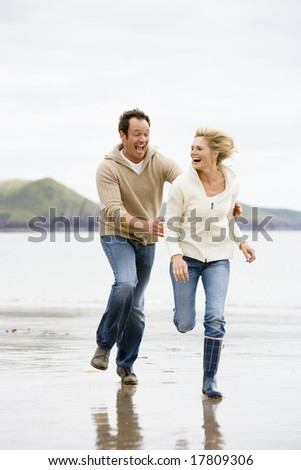 Couple running on beach holding hands smiling