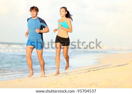 Couple running on beach. Runners jogging during outdoor workout on beautiful beach at sunset. Caucasian man, Asian woman.