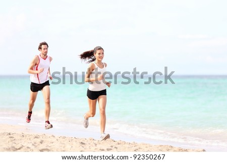 Couple running on beach. Runners jogging outside training. Caucasian / Asian woman runner and Caucasian fitness man model.