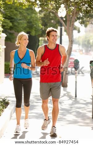 Couple running on city street
