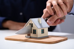 Couple's Hand Cutting The Miniature House Model With Knife On Chopping Board