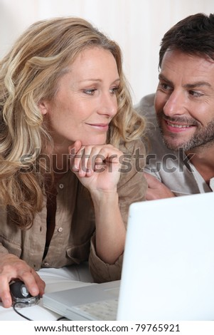 Couple sat by computer