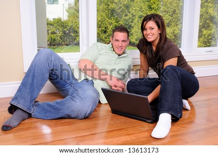 Couple Sat On The Floor Of Their New Home With No Furniture - stock photo