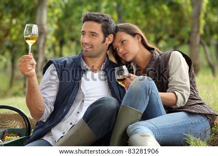 Couple sat tasting wine in vineyard