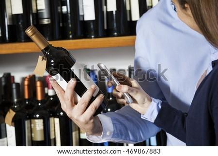Couple Scanning Barcode On Wine Bottle Through Smartphone