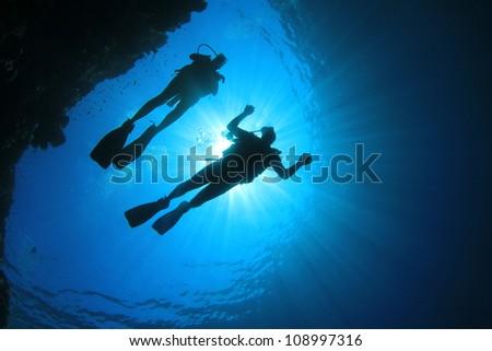 Couple Scuba Diving, silhouettes against sun #108997316