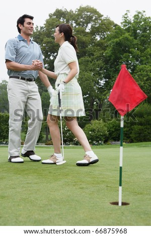 Couple shaking hands on golf course