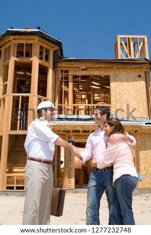 Couple shaking hands with architect in front of partially built house