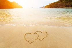 Couple shapes of hearts on sand. Love and romantic honeymoon vacation travel. Valentines drawing on the beach.