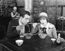Couple sharing a noodle in a restaurant