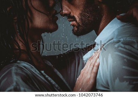 Couple sharing romantic moments under the rain