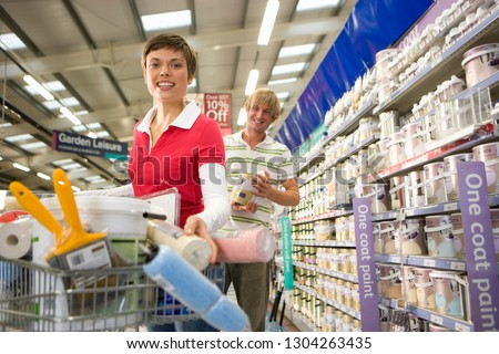 Couple shopping for home decorating materials in DIY store at camera