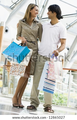 Couple shopping in mall carrying bags